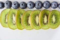 Fila della frutta sulla tavola bianca Immagini Stock