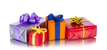 Fila della raccolta dei contenitori di regalo variopinti con gli archi, isolata su bianco Fotografia Stock