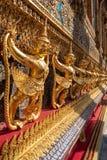 Fila della statua dorata di Garuda sulla bella parete nel tempio reale della Tailandia fotografia stock libera da diritti