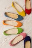 Fila delle ballerine variopinte delle scarpe su un fondo di legno bianco Fotografia Stock Libera da Diritti