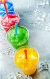 Fila delle bevande variopinte della melma in tazze di plastica Fotografia Stock