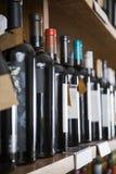 Fila delle bottiglie di vino visualizzate sullo scaffale Immagini Stock