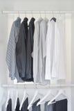 fila delle camice bianche, grige, nere con i pantaloni che appendono nel guardaroba Fotografie Stock Libere da Diritti