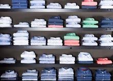 Fila delle camice sugli shelfs nel negozio di vestiti degli uomini Immagine Stock Libera da Diritti
