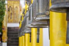 Fila delle campane bronzee fuori di un tempio buddista dorato Fotografia Stock