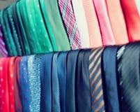 Fila delle cravatte sui ganci nel negozio di vestiti degli uomini Fotografie Stock