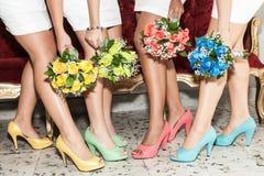 Fila delle damigelle d'onore con i mazzi dei fiori e delle scarpe dei colori differenti Fotografie Stock