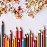 Fila delle matite colorate e delle rasature della matita su una carta fotografie stock
