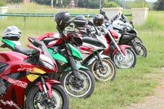 Fila delle motociclette parcheggiate colourful su erba verde Fotografia Stock Libera da Diritti