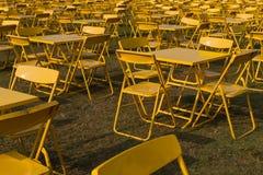 Fila delle sedie e delle tavole del metallo giallo nell'abbondanza Fotografie Stock Libere da Diritti