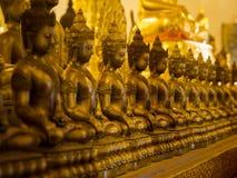 Fila delle statue di Buddha al tempio buddista Fotografie Stock Libere da Diritti