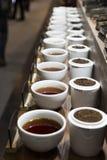 Fila delle tazze di tè, vari generi di tè Immagine Stock