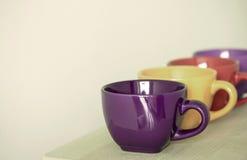 Fila delle tazze variopinte sulla tavola Immagine Stock