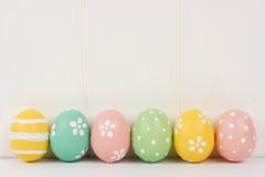 Fila delle uova di Pasqua sopra legno bianco Fotografie Stock