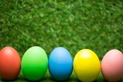 Fila delle uova di Pasqua su erba Immagini Stock