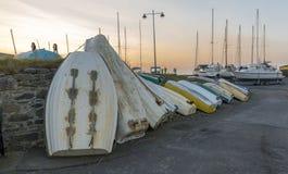 Fila di dinghy& rovesciato x27; s, contro una parete, con un fondo di un tramonto Fotografia Stock