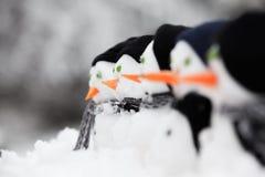 Fila di mini pupazzi di neve con i cappelli Immagini Stock