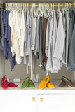 Abbigliamento casual sui ganci e sulle scarpe al negozio. Fotografia Stock Libera da Diritti
