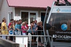 A fila dos turistas que aterram no carrossel Sochi da montanha do teleférico do elevador Imagens de Stock Royalty Free