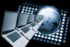 Fila e globo dei computer portatili Immagine Stock