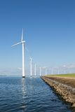 Fila larga de las turbinas de viento de la orilla en el mar holandés Fotos de archivo