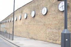 Fila lunga degli orologi su un alto muro di mattoni fotografia stock