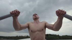 Fila muscular del hombre fuerte del barco viejo, flotando en un barco con los remos Cámara lenta almacen de metraje de vídeo