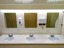 Fila pubblica leggermente grungy della toilette dei lavandini immagine stock
