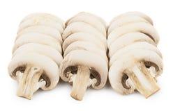 Fila tres de los champiñones crudos aislados en blanco fotos de archivo