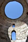 Fila vertical de tres ventanas en la pared blanca, con el cielo azul brillando a través foto de archivo