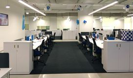 Fila y ordenadores de la silla en la estación de trabajo una empresa de tecnología de la información fotografía de archivo