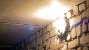 Filament Bulb Lights Up on a Stone Wall stock video