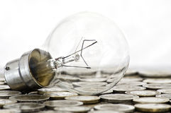 Filament bulb lying on coins Stock Images