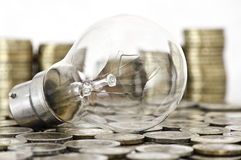 Filament bulb lying on coins Royalty Free Stock Image