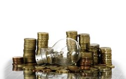 Filament bulb lying on coins Royalty Free Stock Photography