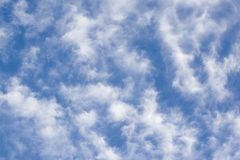 Filament cloud. Fluffy strecth cloud on blue background Stock Photos