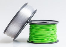 Filament for 3D Printer crystal clear and bright green against a. Bright background stock image