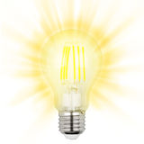 Filament LED bulb. Glowing yellow light LED filament bulb on a white background Royalty Free Stock Photos