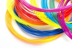 Filamentos plásticos do arco-íris colorido com para a pena 3D que coloca no fundo branco Brinquedo novo para a criança Imagem de Stock Royalty Free