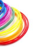 Filamentos plásticos do arco-íris colorido com para a pena 3D que coloca no fundo branco Brinquedo novo para a criança Fotografia de Stock Royalty Free