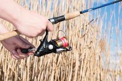 Filando nelle mani del pescatore Primo piano dell'attrezzatura per la pesca e dell'erba alta asciutta Fotografia Stock