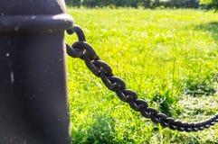 filar z żelazo łańcuchem na trawy tle przemysłowy, natura Zdjęcia Stock