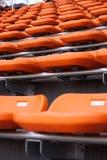 Filas de asientos anaranjados vacíos en un estadio Foto de archivo