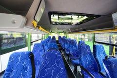 Filas de asientos suaves dentro del salón del autobús vacío de la ciudad Fotos de archivo
