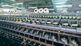 Filas de carretes, haciendo girar en las máquinas de la fábrica de la materia textil almacen de video