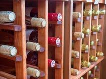 Filas de las botellas de vinos blancos rojos y en el estante de madera del vino fotografía de archivo