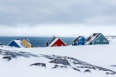 Filas de las casas coloridas del inuit entre rocas en un suburbio del ártico Imagen de archivo