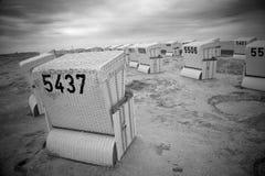 Filas de las sillas de playa de mimbre cubiertas abandonadas Imagenes de archivo