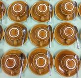 Filas de las tazas de café al revés en el platillo Fotos de archivo