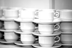 Filas de las tazas de café con los platillos Imagenes de archivo
